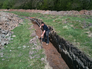 Ashley in a trench laying a ground loop collector pipe in Whitchurch, Shropshire